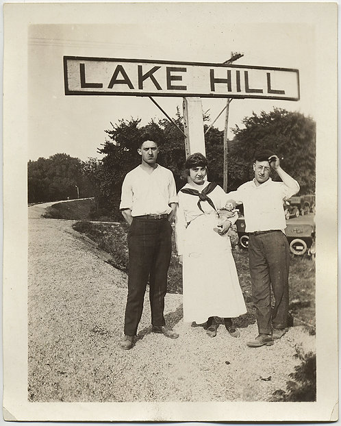 STRANGE UNHAPPY THREESOME STANDS at LAKE HILL SIGN w KEWPIE DOLL in ARM