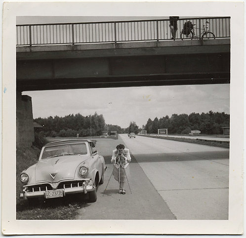 WOMEN SETS UP CAMERA w TRIPOD on SIDE of GERMAN ROAD to SHOOT HOME MOVIE