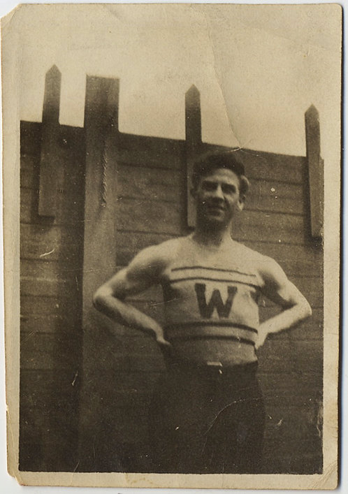 "ATHLETE in LETTER VEST ""W"" against WOODEN FENCE ARMS AKIMBO"