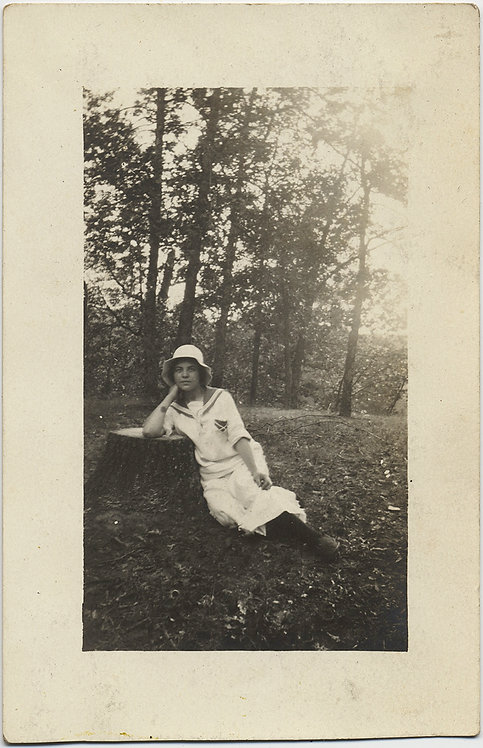 YOUNG WOMAN in SAILOR SUIT LEANS and LIES AGAINST TREE STUMP in STUDIED POSE