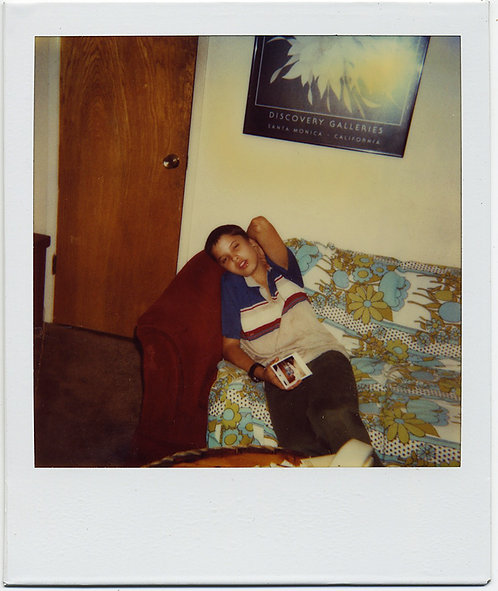 KID w POLAROID LIES on COUCH w COLORED FLORAL COVERING