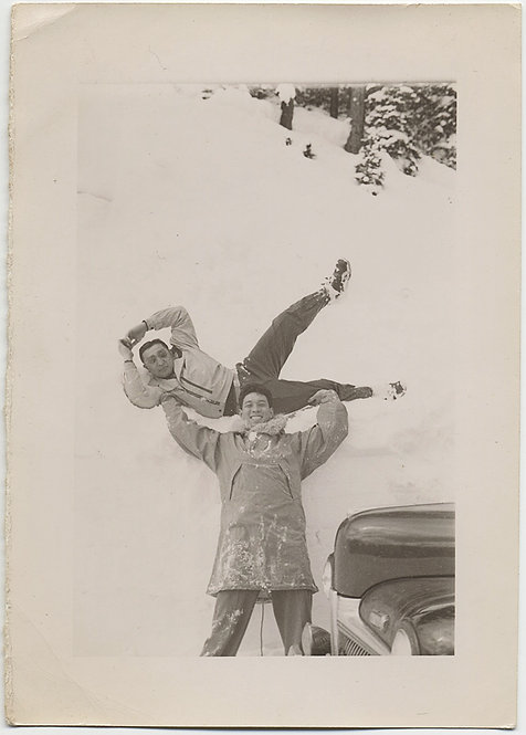 TRICK PHOTO HIGH ANGLE BOY LIFTS HANDSOME GUY above HEAD in SNOW