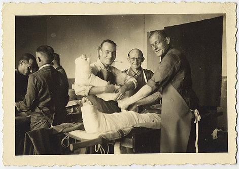 SMILING MEN MEDICS GRASP TWO LEGS in PLASTER CASTS INJURED SOLDIER?