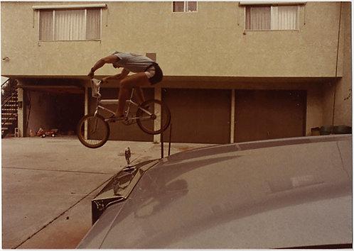 BMX? STUNT BIKE BICYCLE RIDER in MID-AIR JUMP SUSPENSION CADILLAC