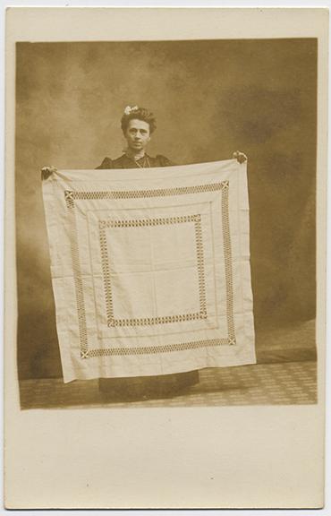 fp2762(RPPC_Woman_HoldingOpenworkTableCloth)