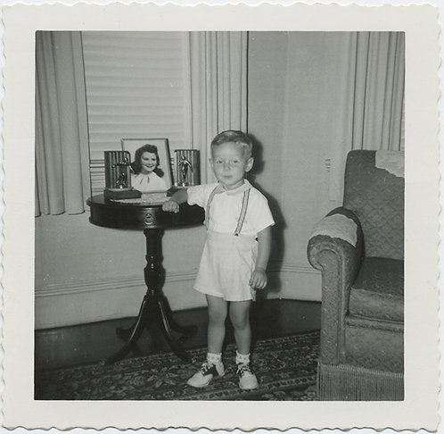 KID in SUSPENDERS poses near table w. PICS