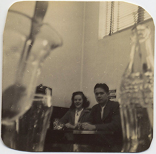 LOW ANGLE SHOT of COUPLE in CAFE with COKE BOTTLE & FLOAT/SUNDAE GLASS