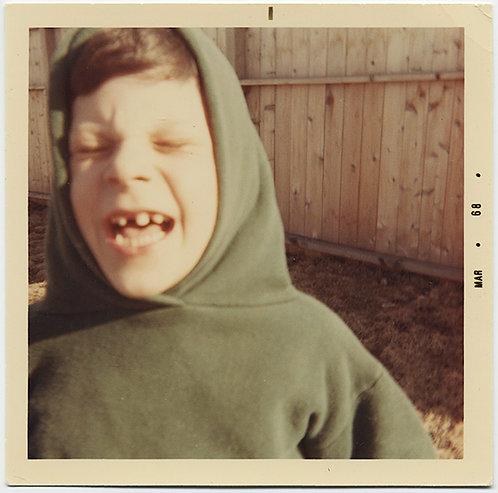 GRIMACING CLOSE-UP BOY WITH GAP TEETH GRIMACES in HOODIE
