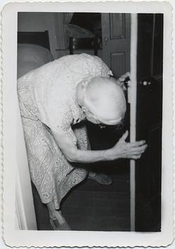 fp6203(OldWOman_BentOverClutchingDoorForSupport_Bedroom)