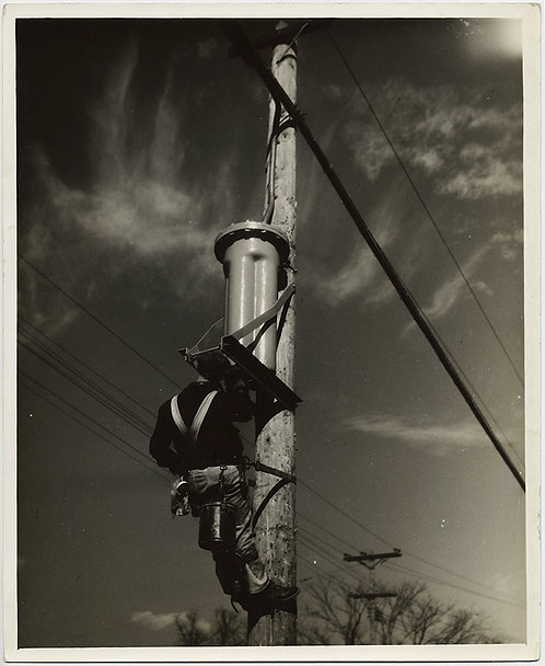 ELECTRICAL LINEMAN up POLE AGAINST CIRRUS CLOUDED SKY