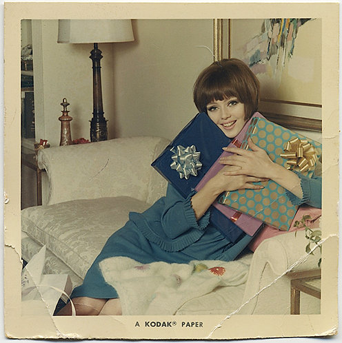 BOB-HAIRED 70's WOMAN CLUTCHES PRESENTS on WHITE COUCH