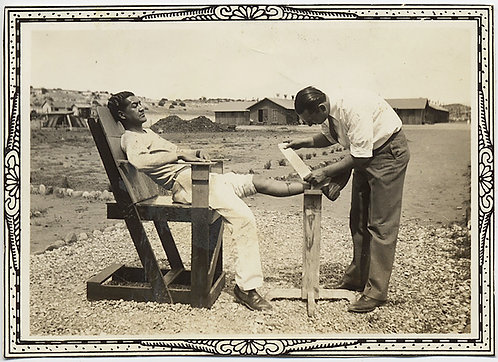 MAN BANDAGES BUDDY'S WOUNDED LEG on WOODEN CHAIR OUT in the FIELD
