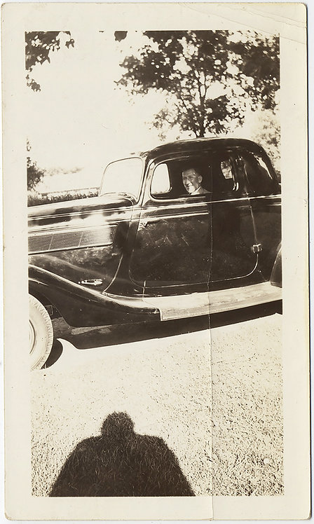 HULKING SHADOW of PHOTOGRAPHER OBSERVES MAN TRAPPED in VINTAGE CAR