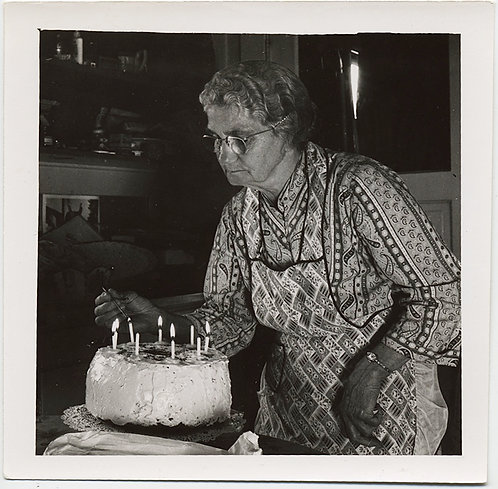 DOUR OLDER WOMAN in RIOTOUS PATTERNED SHIRT APRON COMBO LIGHTS BIRTHDAY CAKE