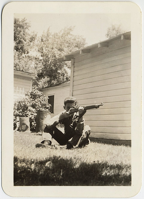 YOUNG MAN SITS on SUBURBAN LAWN AIMS RIFLE at UNKNOWN TARGET