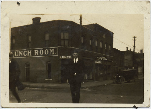 SIGNAGE YOUNG MAN STANDS in STREET w HOTEL & LUNCH ROOM BEHIND