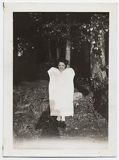 STRANGE WOMAN FRAMES FACE HOLDS UP WHITE SHEET against DARK FOREST BACKGROUNF