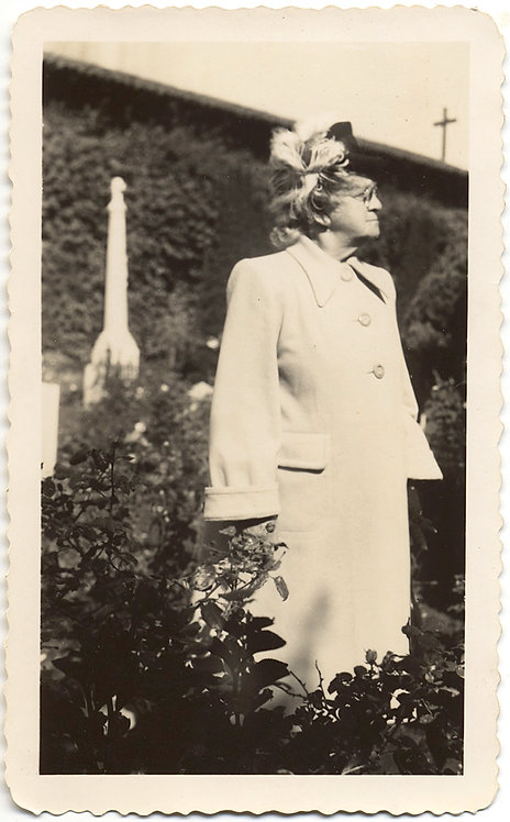 STERN WOMAN in GRAVEYARD FOLIAGE LOOKS into DISTANCE MONUMENT BEHIND HAT ABOVE