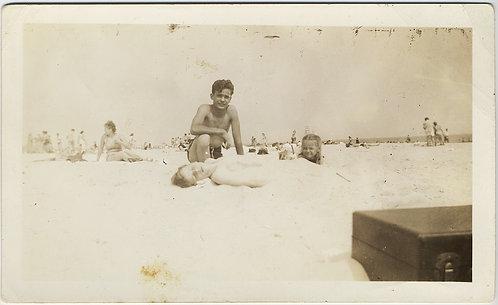 """STRANGE PALE WHITE KID LIES """"DEAD"""" on BEACH SAND w WEIRD SUITCASE in FRAME"""