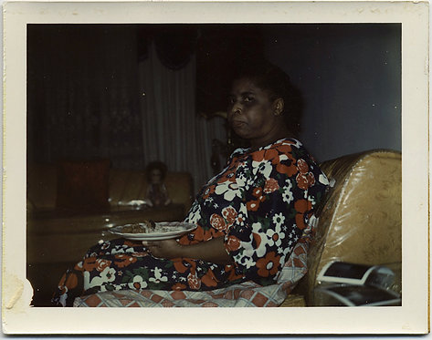 POLAROID DISTRUSTFUL AFRICAN AMERICAN WOMAN EATS on PLASTIC COVERED SOFA