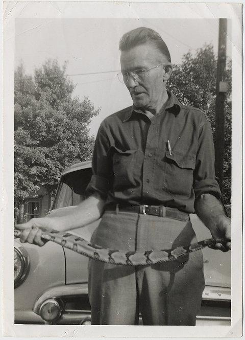 SNAKE HANDLER MAN HOLDS LONG SNAKE & VINTAGE CAR