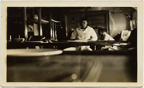 LOW ANGLE SHOT fm TABLE among PLATES in SHIP'S GALLEY SHOWS SAILORS MESS EATING