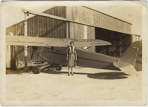 WOMAN AVIATOR? STANDS by VINTAGE AIRPLANE at HANGAR