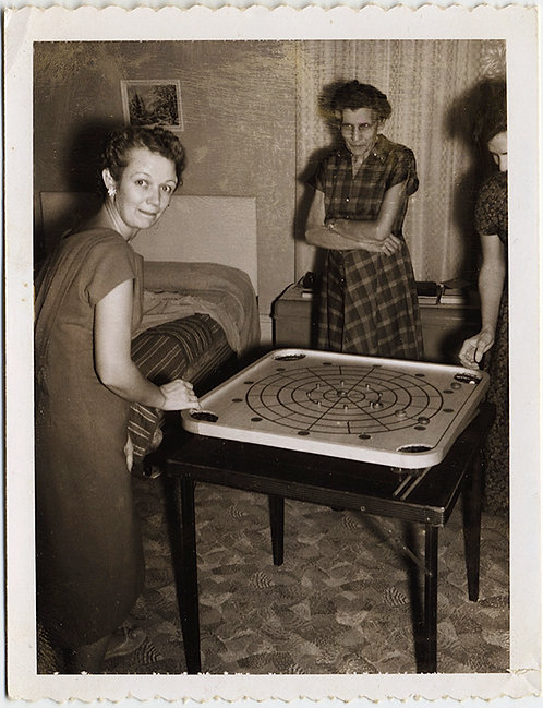 POLAROID WOMEN PLAY CARROM while UNCONVINCED OLDER WOMAN GLOWERS WATCHING