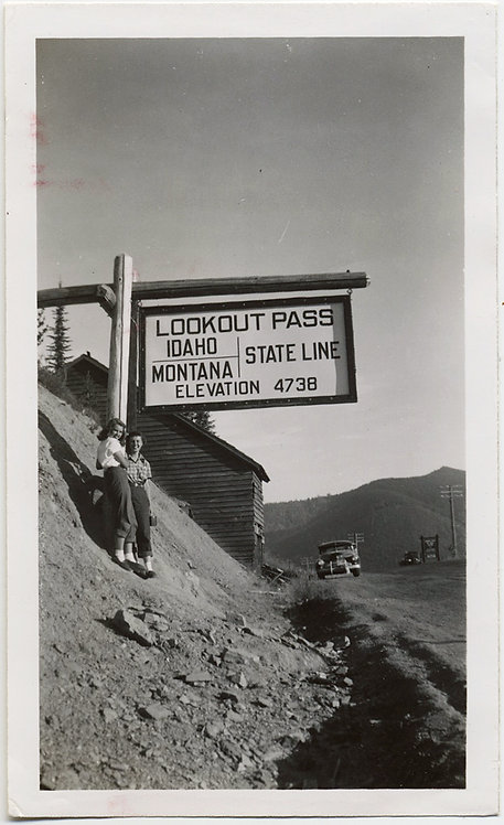 LOVELY WOMEN POSE at LOOKOUT PASS IDAHO MONTANA STATE LINE SIGN