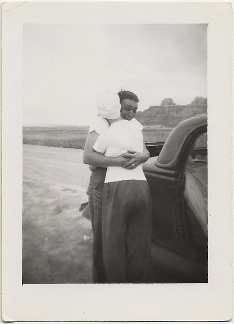 TOUCHING AFFECTIONATE COUPLE HUGS next to VINTAGE CAR in DESOLATE LANDSCAPE