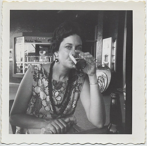 WOMAN in FLORAL DRESS SIPS BEER in FOREIGN LAND