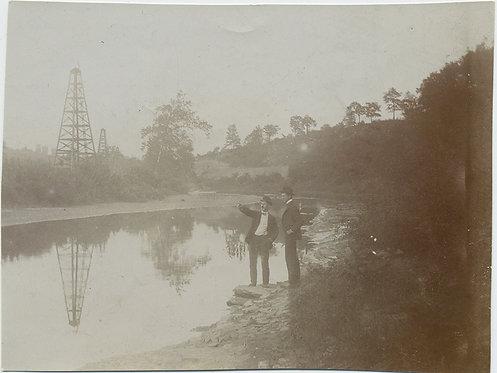 TWO MEN PROSPECTORS ADMIRE LANDSCAPE & EARLY OIL DERRICKS RIVER REFLECTION