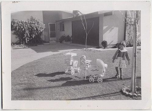 STRANGE LOPSIDED CHILD WEARING 1 ROLLERSKATE & WHITE DOLL STUFF in SUBURBAN YARD