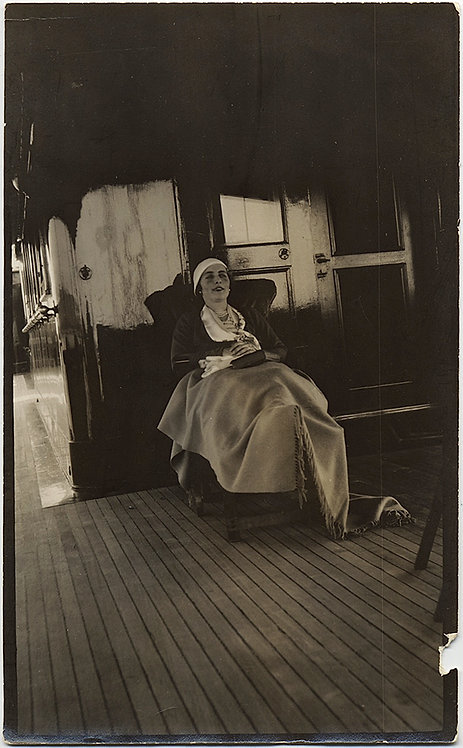 TRAVELING WOMAN on DECKCHAIR in BLANKET RELAXES on SHIP'S DECK