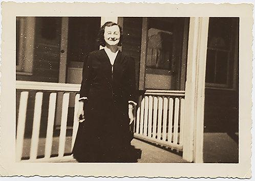 CARTOON-FACED WOMAN Aunt Neliie SMILES against PORCH RAILINGS