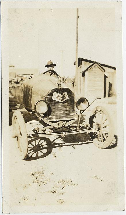 MAN at the WHEEL of BATTERED SPINDLY VINTAGE CAR JALOPY
