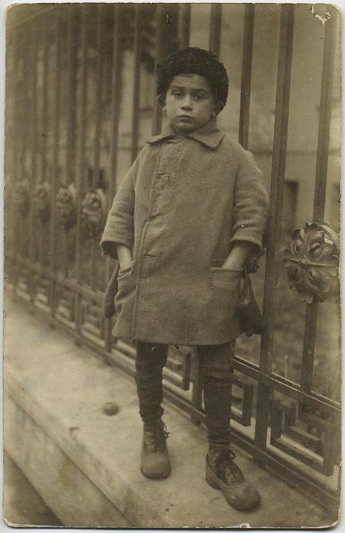 MOVING PORTRAIT of STREET KID LITTLE BOY against IRON RAILING