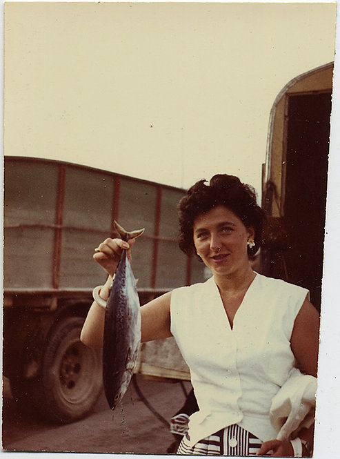 ICONIC WOMAN HOLDS up FISH in CLASSIC FISHING PORTRAIT