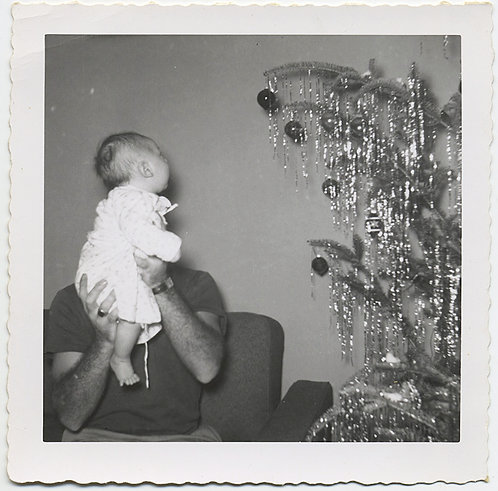 HIDDEN DAD HOLDS up BABY in front of OBSCURING FACE ADMIRING XMAS TREE TINSEL