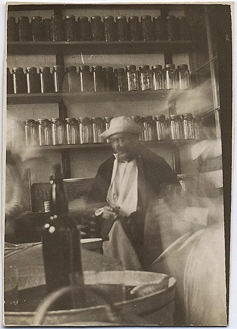 """STRANGE MAN in HAT in ROOM FULL OF JARS & BOTTLE """" After Treatment"""" 1931 CAPTION"""