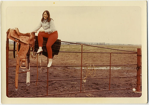 YOUNG WOMAN in RED TIGHTS SITS SIDE SADLLE w SADDLES on METAL PASTURE GATE