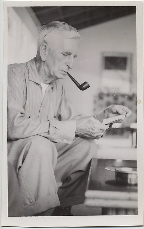 CONTEMPLATIVE FOCUSED OLDER MAN SMOKING PIPE EVALUATES SNAPSHOTS?