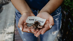 """Photo by Katt Yukawa of hands holding coins, with a note saying """"Make a change"""""""