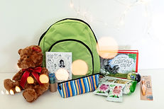 Teddy bear, books, pencil case and small supplies for kid's pack in front of a green back pack.