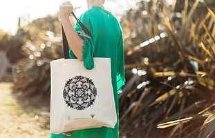 Photo of a person walking outside holding a tote bag. The bag has a mandala pattern printed on it.