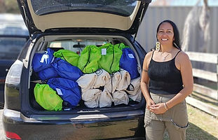 A volunteer stands in front of her car boot, which is loaded up with bags filled with care supplies.