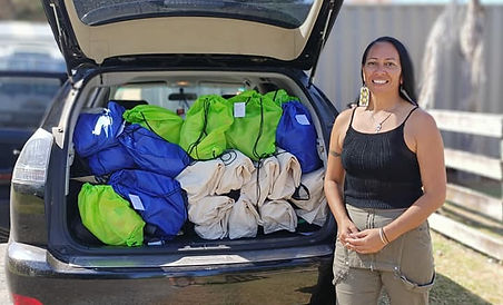 Ninakaye stands in front or a car loaded up with bags to go to a refuge.