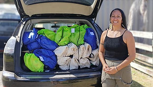 Volunteer standing in front of car loaded with packs