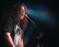 James Deveau singing into a mic
