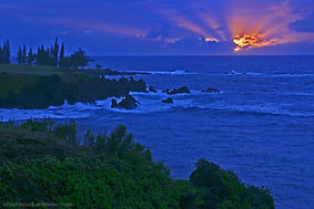 The sun rises through a cloudy horizon of the Pacific Ocean from Maka Alae Point on the Hawaiian island of Maui